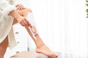 Frau rasiert sich die Beine mit einem Nassrasierer